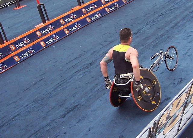 Man pushing his racing wheelchair at a triathalon.